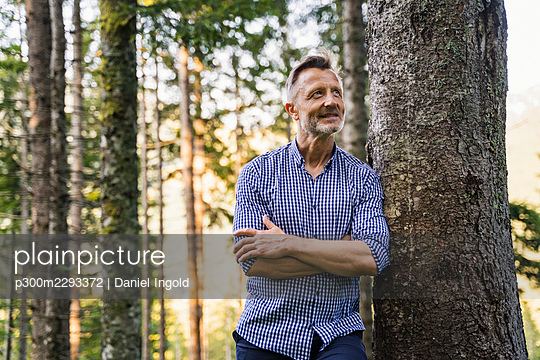 Smiling man with arms crossed leaning on tree trunk - p300m2293372 by Daniel Ingold