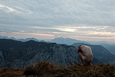 Naked man in the mountains squats huddled on the ground - p1383m1537766 by Wolfgang Steiner