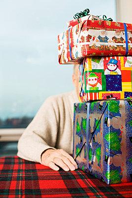 Senior man hidden behind Christmas presents - p3720440 by James Godman