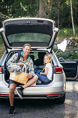 Portrait of smiling father with picnic basket by daughter sitting in car trunk - p426m2212167 by Maskot