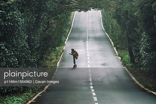 Man skateboarding on road amidst forest at Garajonay National Park - p1166m1554963 by Cavan Images