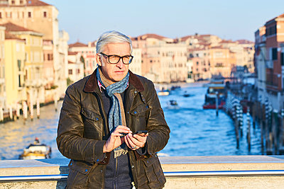 Man writes SMS on a bridge in Venice - p1312m2082156 by Axel Killian