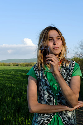 Young woman smoker with cigarette in field  - p1363m2013503 by Valery Skurydin