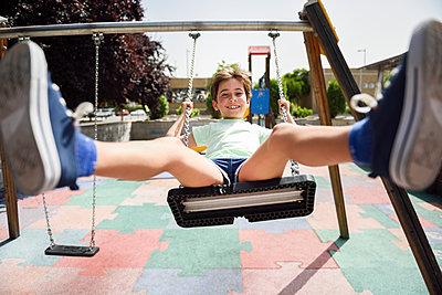 Portrait of smiling little girl having fun on a swing - p300m2029452 von Javier Sánchez Mingorance