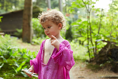 Little girl wearing pink tunic in nature holding horse figurine - p300m2102645 von Antje Merkel