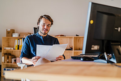 Businessman reading document at desk in wooden open-plan office - p300m2170069 by Daniel Ingold