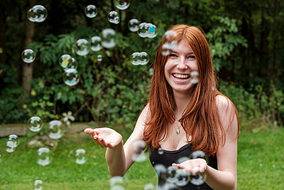 Happy woman playing with soap bubbles in backyard - p300m2226015 by Lisa und Wilfried Bahnmüller