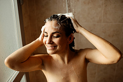 Portrait of adult woman smiling while taking shower - p300m2265641 by Gala Martínez López