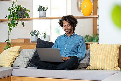 Businessman using laptop while sitting cross legged on sofa at home - p300m2276581 by Steve Brookland