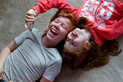 Portrait of brother and sister lying on the floor taking selfies with smartphone - p300m948853 by Lisa und Wilfried Bahnmüller