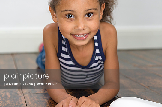 Six year old girl lying on floor with a book in front of her - p1433m2071754 by Wolf Kettler