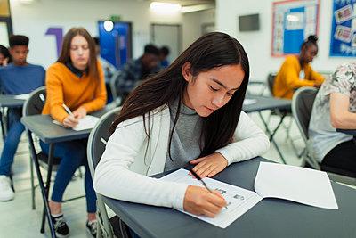 Focused high school girl student taking exam at desk in classroom - p1023m2190083 by Paul Bradbury