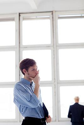 Junger Mann grübelt im Büro  - Kollegin im Hintergrund - p1212m1115607 von harry + lidy