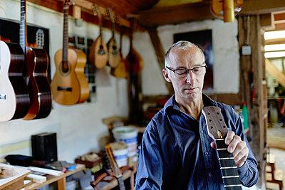 Gitarrenbauer untersucht eine Gitarre in seiner Werkstatt - p1359m1221834 von Great Images