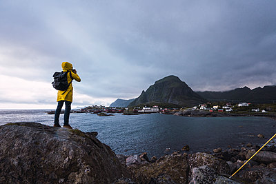 Norway, Lofoten, rear view of man standing on a rock at the coast taking a picture - p300m2042276 by Kike Arnaiz