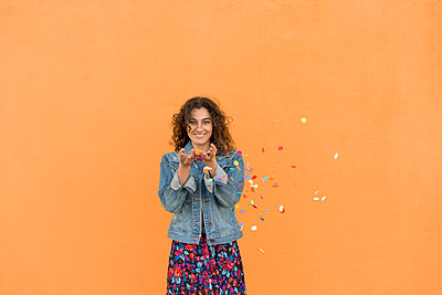 Portrait of smiling young woman throwing confetti in the air in front of orange wall - p300m2102510 von VITTA GALLERY