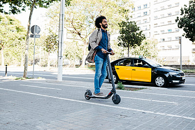 Man with backpack riding his E-Scooter on a bicycle lane - p300m2114506 by Josep Rovirosa