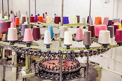 Multicolored cotton reels on a machine in a factory - p300m2167476 von Floco Images