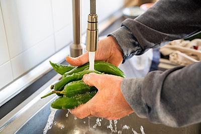 Senior man washing vegetables in kitchen sink at home - p300m2264497 by VITTA GALLERY