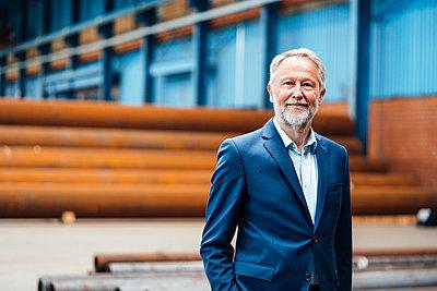 Senior businessman standing in factory - p300m2299344 by Joseffson