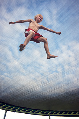 Low angle view of boy jumping on trampoline - p312m1113994f by Johan Willner