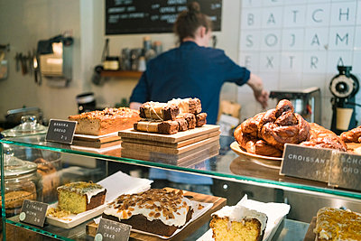 Barista, man working in a coffee shop, counter with pastries and cakes. - p429m2182692 by Tamboly