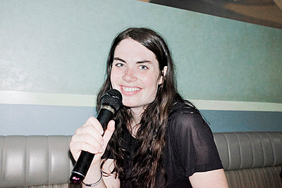 Young woman singing karaoke - p956m1044306 by Anna Quinn