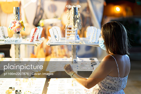 woman buying a bracelet in the beach shop - p1166m2207876 by Cavan Images