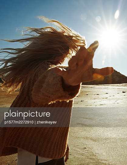 Blonde woman turns towards the sun with outstretched arms - p1577m2272910 by zhenikeyev