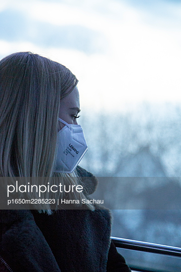 Young woman with FFP2 mask looking out of the train window - p1650m2285223 by Hanna Sachau
