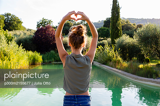 Rear view of a girl standing at swimming pool, forming a heart with her hands - p300m2155677 by Julia Otto