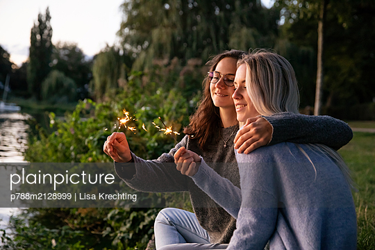 Two girlfriends with sparklers on the river bank - p788m2128999 by Lisa Krechting