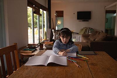 Girl doing her homework at home - p1315m2056247 by Wavebreak