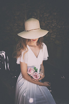 Young woman with big straw hat and roses - p1445m2184796 by Eugenia Kyriakopoulou