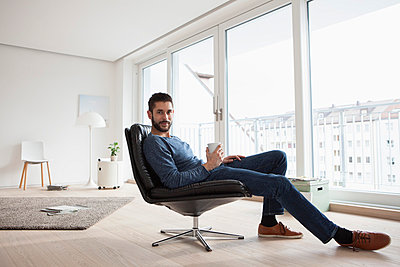 Young man relaxing on leather chair with cup of coffee - p300m1047743f by Rainer Berg