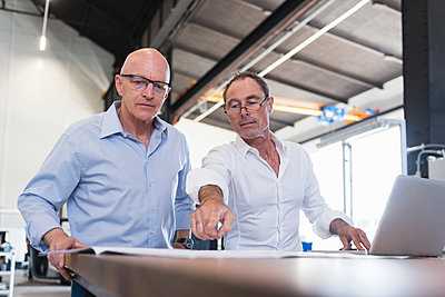 Two businessmen looking at plan on table in factory - p300m1460050 by Daniel Ingold