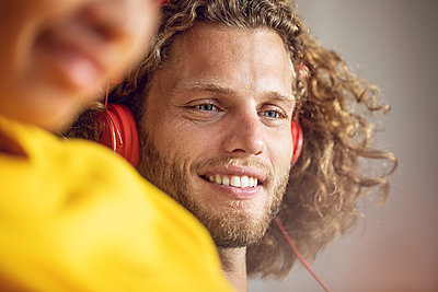 Portrait of smiling young man listening to music with woman in foreground - p300m2156504 von Maya Claussen
