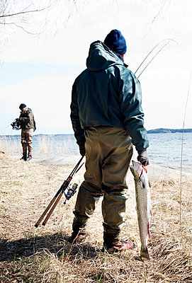 Fishermen Wearing Waders Equipment On The Beach; With A Catch In Hand; Wild Trout   - p847m988240 by Maria Annas