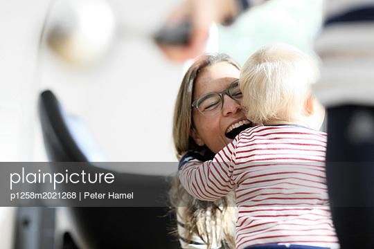 Kleinkind umarmt Mutter - p1258m2021268 von Peter Hamel