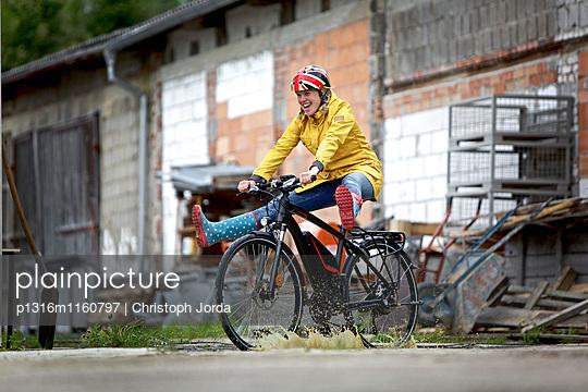Junge Frau fährt mit einem elektrischen Fahrrad durch eine Pfütze, Tanna, Thüringen, Deutschland - p1316m1160797 von Christoph Jorda