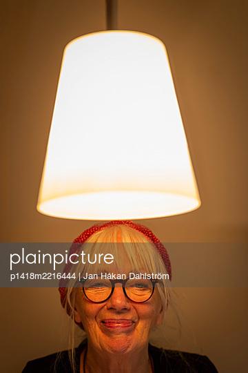Happy woman under ceiling light - p1418m2216444 by Jan Håkan Dahlström