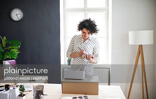 Smiling young woman preparing a package at desk - p300m2144034 von HalfPoint