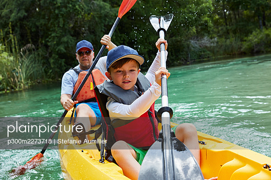 Cute boy and father canoeing in lake during vacation - p300m2273718 by Stefanie Aumiller