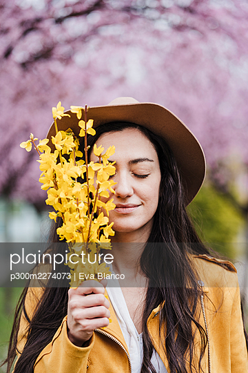 Smiling woman with eyes closed holding yellow flowers during springtime - p300m2274073 by Eva Blanco