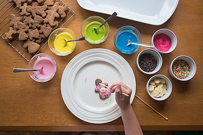 Young girl decorating gingerbread with frosting - p1166m2137157 by Cavan Images