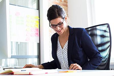 Smiling businesswoman at desk in office - p300m2012515 by Florian Küttler