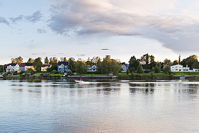 Sweden, Vasterbotten, Umea, Motorboats on river and houses at sunset - p352m1127021f by Jonas Gunnarsson