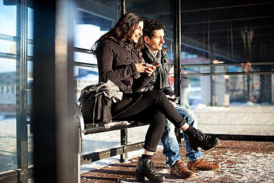 Happy friends in warm clothes holding mobile phones while looking away - p426m766616f by Maskot