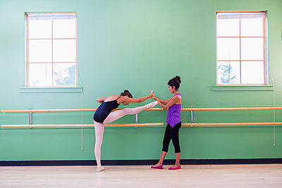 Mixed race ballerina practicing with teacher at barre - p555m1463777 by Marc Romanelli