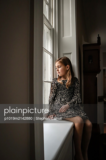 Mädchen sitzt auf der Fernsterbank - p1019m2142880 von Stephen Carroll
